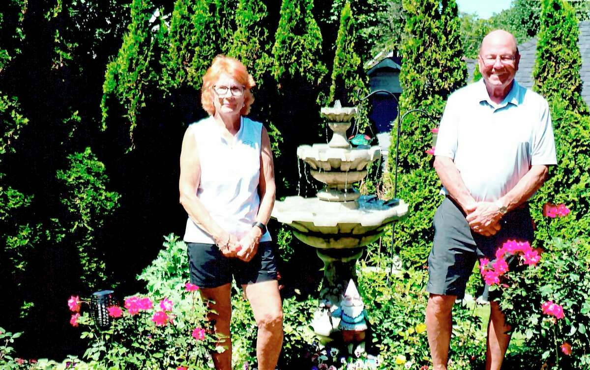 Mary Metzger (not pictured), a member of Spirit of the Woods Garden Club, Inc., presented Onaleeand Tom Ruddy with the club's Garden of the Month Award. (Courtesy photo)