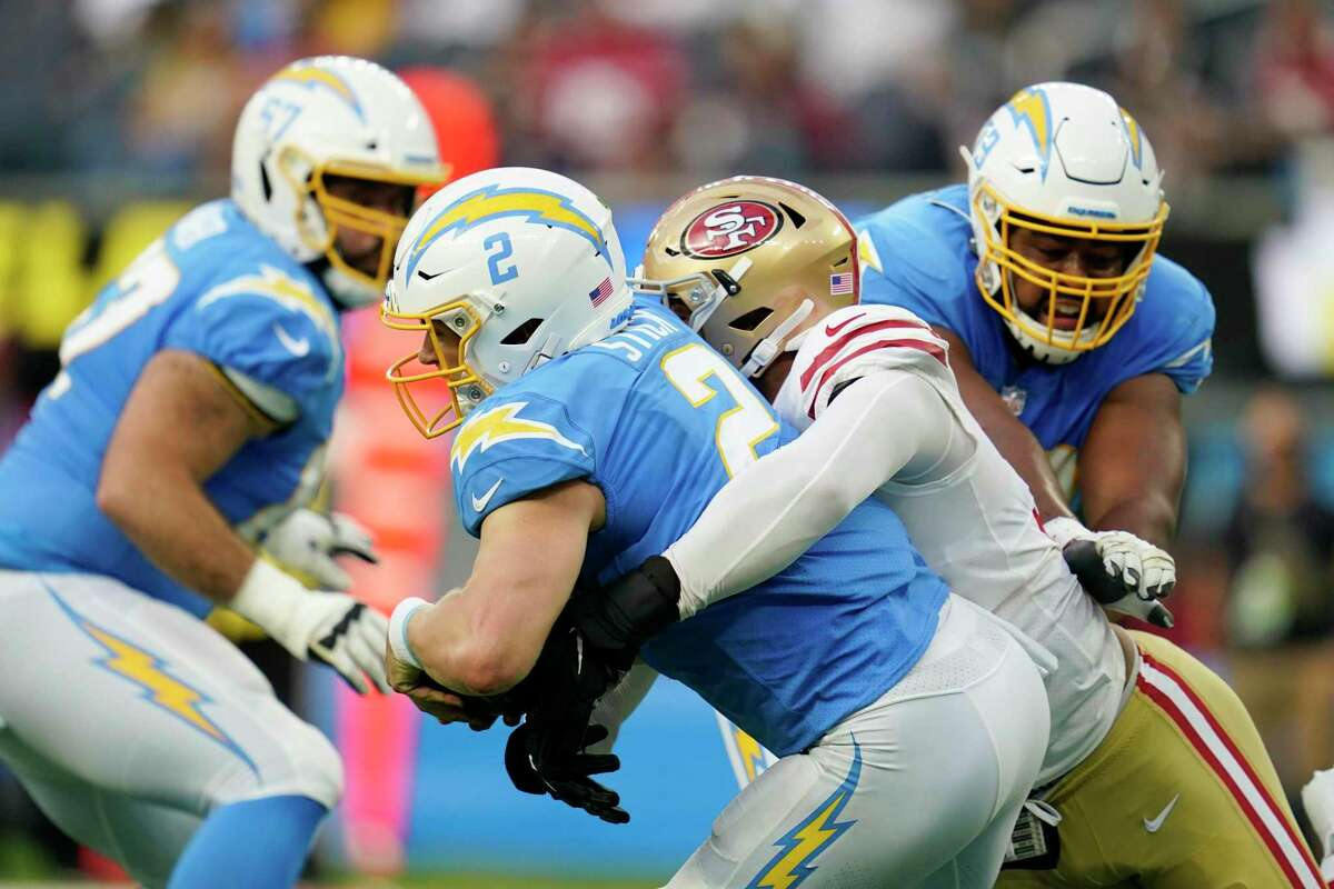Los Angeles Chargers quarterback Easton Stick (2) is sacked by San Francisco 49ers defensive end Jordan Willis for a safety during the first half of a preseason NFL football game Sunday, Aug. 22, 2021, in Inglewood, Calif. (AP Photo/Ashley Landis)
