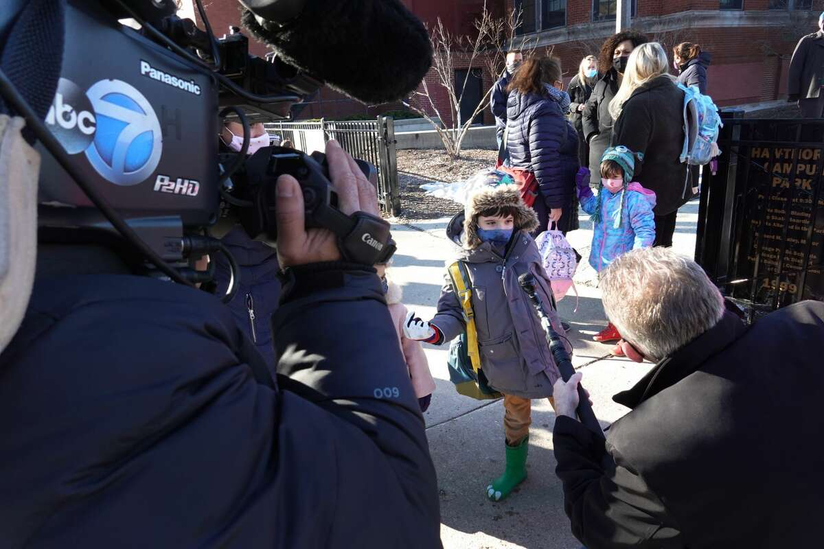 Children are interviewed by a television news reporter as they leave Hawthorne Scholastic Academy following their first day of in-person learning on March 01, 2021 in Chicago, Illinois. (Photo by Scott Olson/Getty Images)