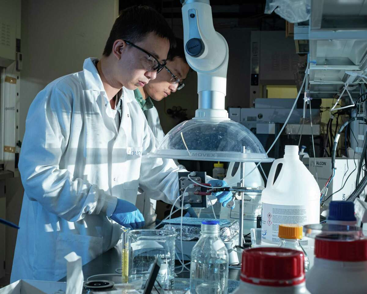 Rice University postdoctoral researcher Chuan Xia, left, and chemical and biomolecular engineer Haotian Wang adjust their electrocatalysis reactor to produce liquid formic acid from carbon dioxide.