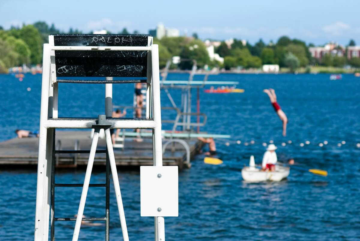 An empty lifeguard chair with a dock in the background and a diver jumping off the diving board into the water at Green Lake in Seattle.