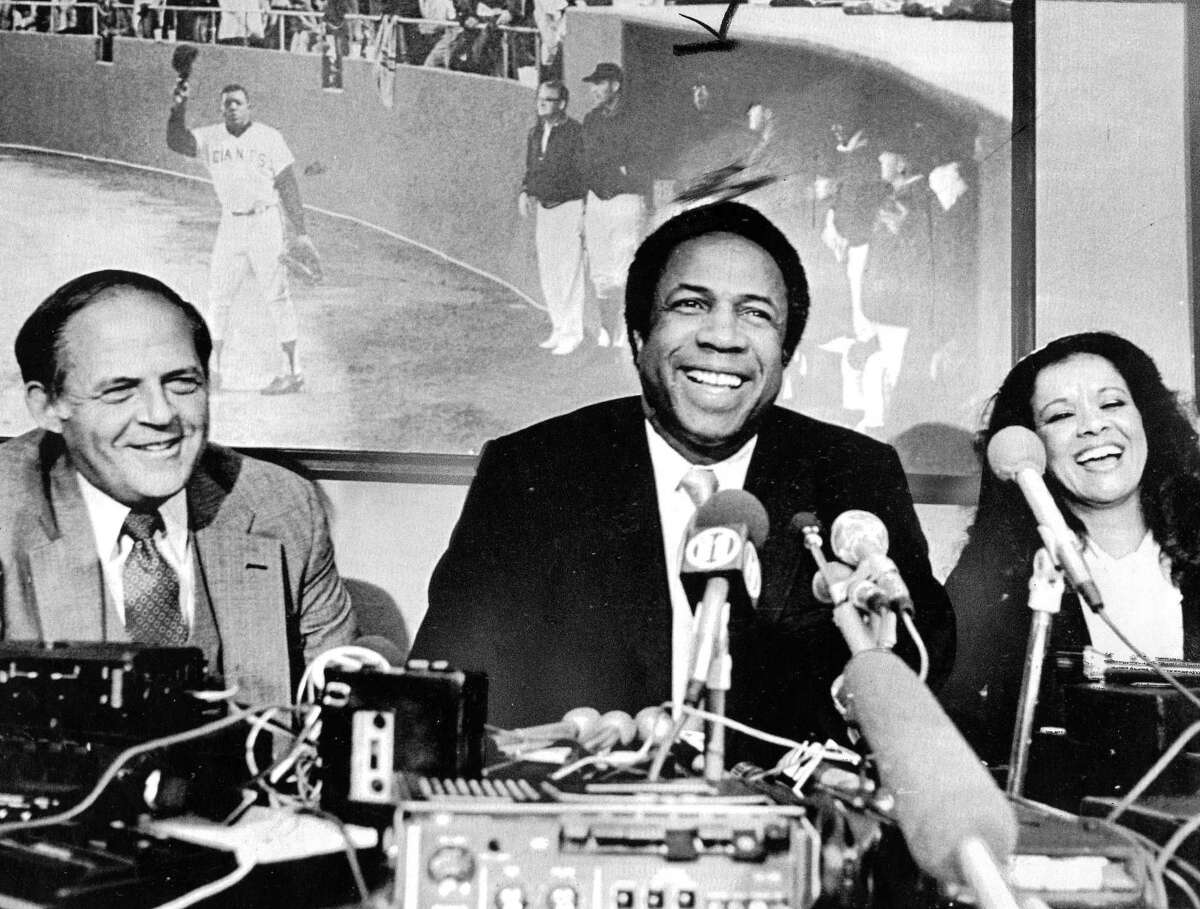 Frank Robinson is hired by the San Francisco Giants to be manager. To his left os Giants owner Bob Lurie, and to his right is wife barbara January 14, 1981 Associated Press Photo Photo ran 1/15/1981, p. 51