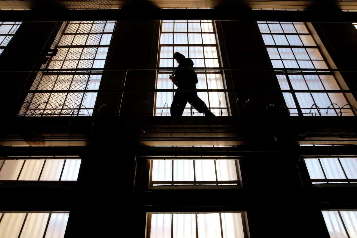 A guard on the catwalk above cells at San Quentin State Prison in San Quentin, Calif. The family of a San Quentin prison guard who died from a COVID-19 infection following the transfer of inmates from another prison in Southern California filed a wrongful death suit against the state prison system.