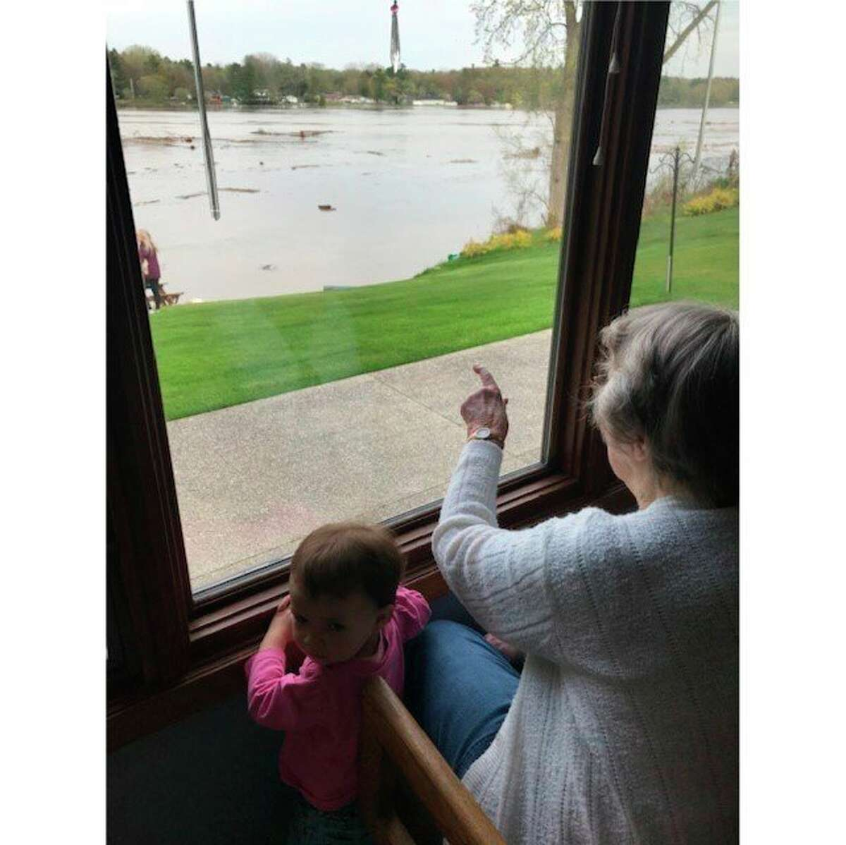 Florence Smith and great-granddaughter Joslyn Smith watch from the window of the home of Bill and Corrine Smith on Sanford Lake during the May 2020 flood. (Photo provided)