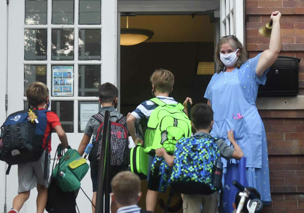 Old Greenwich School Principal Jennifer Bencivengo rings the bell on the first day of the 2020-2021 school year at Old Greenwich School in Old Greenwich, Conn. Wednesday, Sept. 9, 2020.