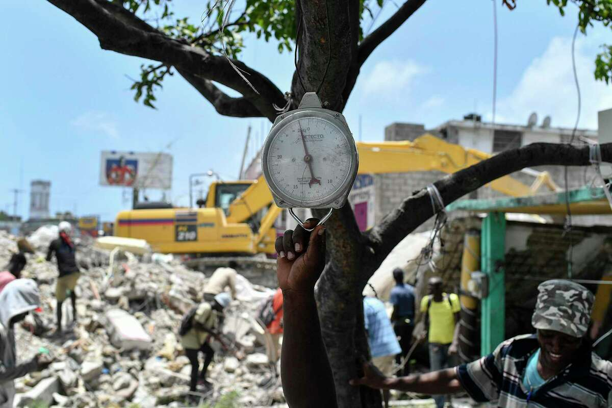 A vendor holds onto a scale as he waits for scavengers to bring him found metal pieces to weigh, at the site of a home that was destroyed by a 7.2 magnitude earthquake, in Les Cayes, Haiti, Saturday, Aug. 21, 2021.