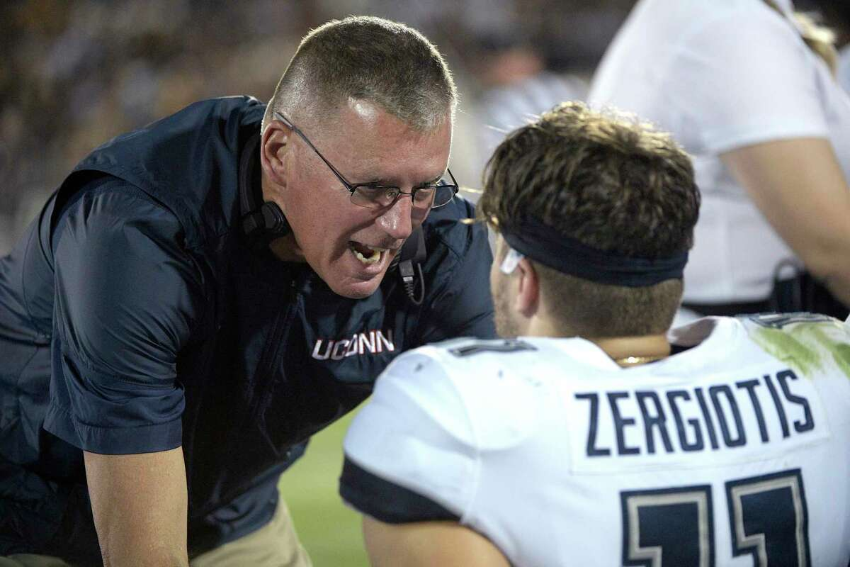 UConn coach Randy Edsall, left, talks to quarterback Jack Zergiotis on the bench during the first half against Central Florida in 2019.