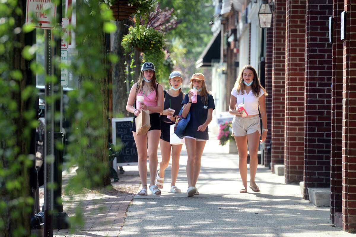 A group of girls walk along a sidewalk on the Post Rd., in Fairfield, Conn. Aug. 24, 2021.