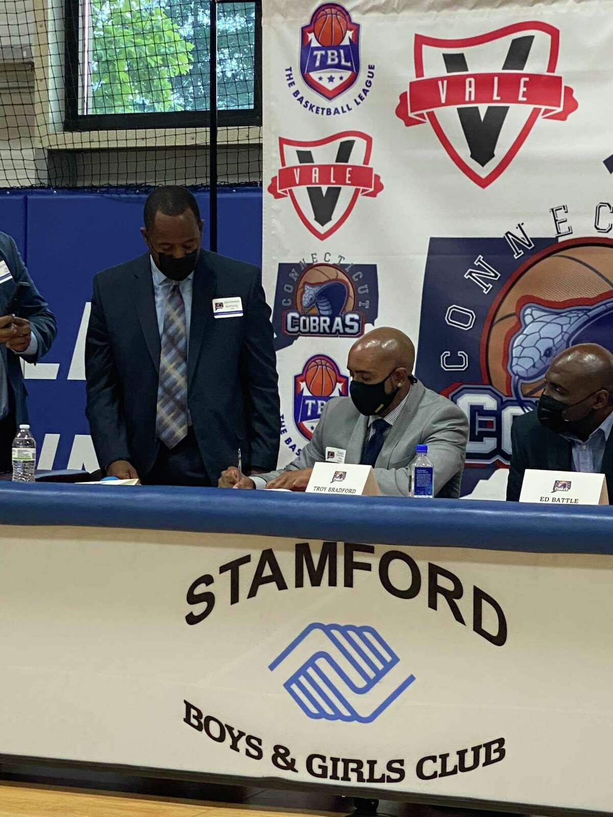 Troy Bradford, center, signs a contract to become the first basketball coach of The Connecticut Cobras of The Basketball League on August 16 at the Boys & Girls Club in Stamford. At left is team owner Anthony Hill. At right is team president Ed Battle.