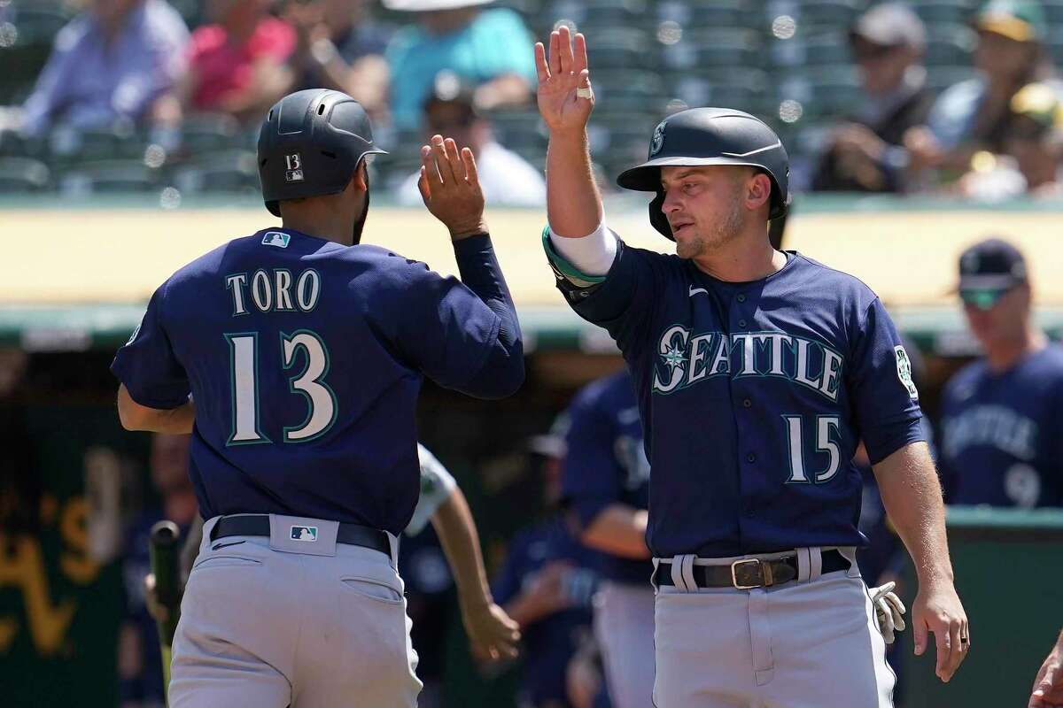 Seattle Mariners' Abraham Toro, left, celebrates with Kyle Seager after both scored on a two-run single by Luis Torrens during the third inning of a baseball game against the Oakland Athletics in Oakland, Calif., Tuesday, Aug. 24, 2021. (AP Photo/Jeff Chiu)