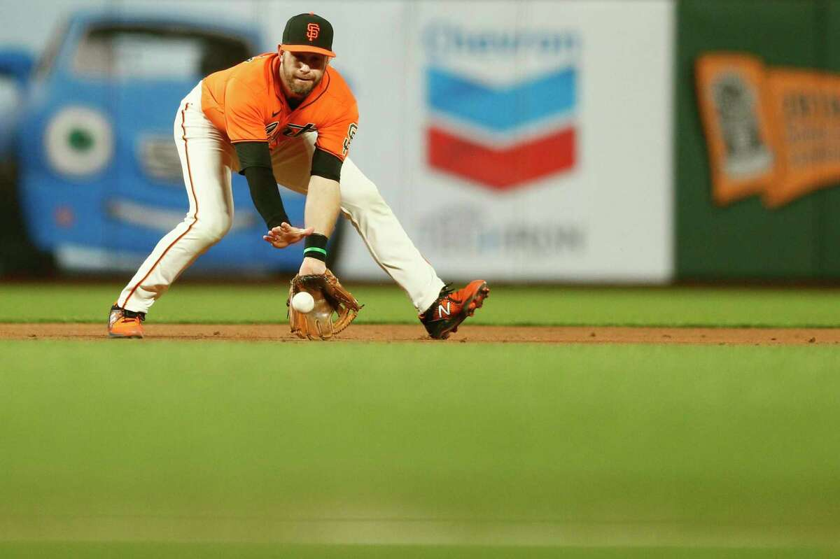 San Francisco Giants third baseman Evan Longoria (10) gloves the ground ball and gets the out at first base in the fifth inning during an MLB game against the San Diego Padres at Oracle Park, Friday, May 7, 2021, in San Francisco, Calif.