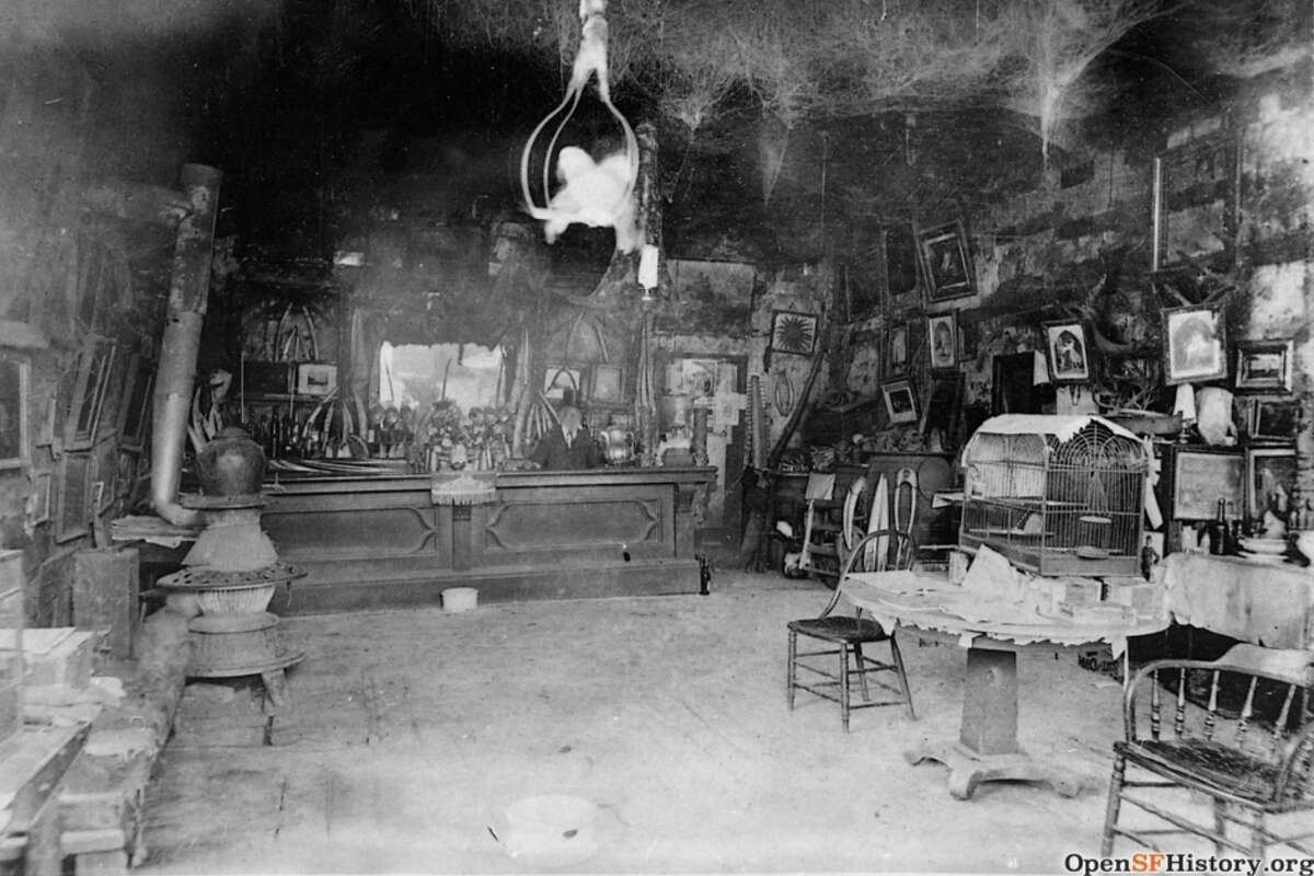 Inside San Francisco's most eccentric bar, Cobweb Place, as seen around 1890. The spider-friendly bar had dense spider webs throughout the space, roaming monkeys and caged parrots, too. It opened in 1856 and closed around the late 1800s.