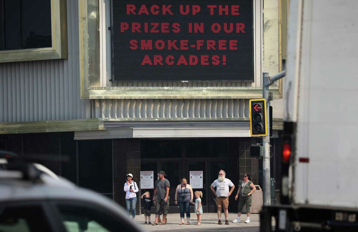 Visitors wait to cross the street at Harvey's Casino, as smoke from several nearby fires fill the Tahoe Basin on in South Lake Tahoe,, Calif.