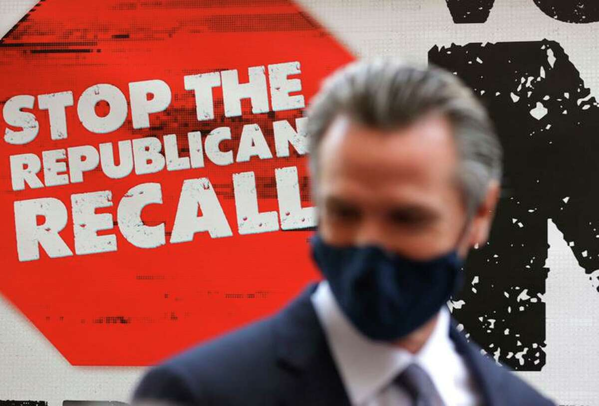 A sign against the recall is posted behind California Gov. Gavin Newsom as he talks with volunteers who are phone banking against the recall at Manny's on Aug. 13 in San Francisco.
