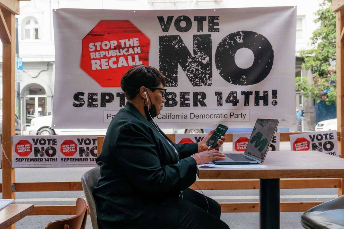 """A volunteer calls voters as part of the """"Vote No"""" campaign urging California voters to vote against the recall of California Gov. Gavin Newsom in San Francisco on Aug. 13."""