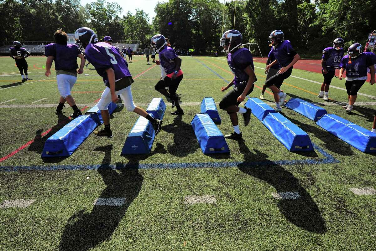 Members of the Westhill High School football team practice at the school in Stamford, Conn., on Tuesday August 24, 2021.