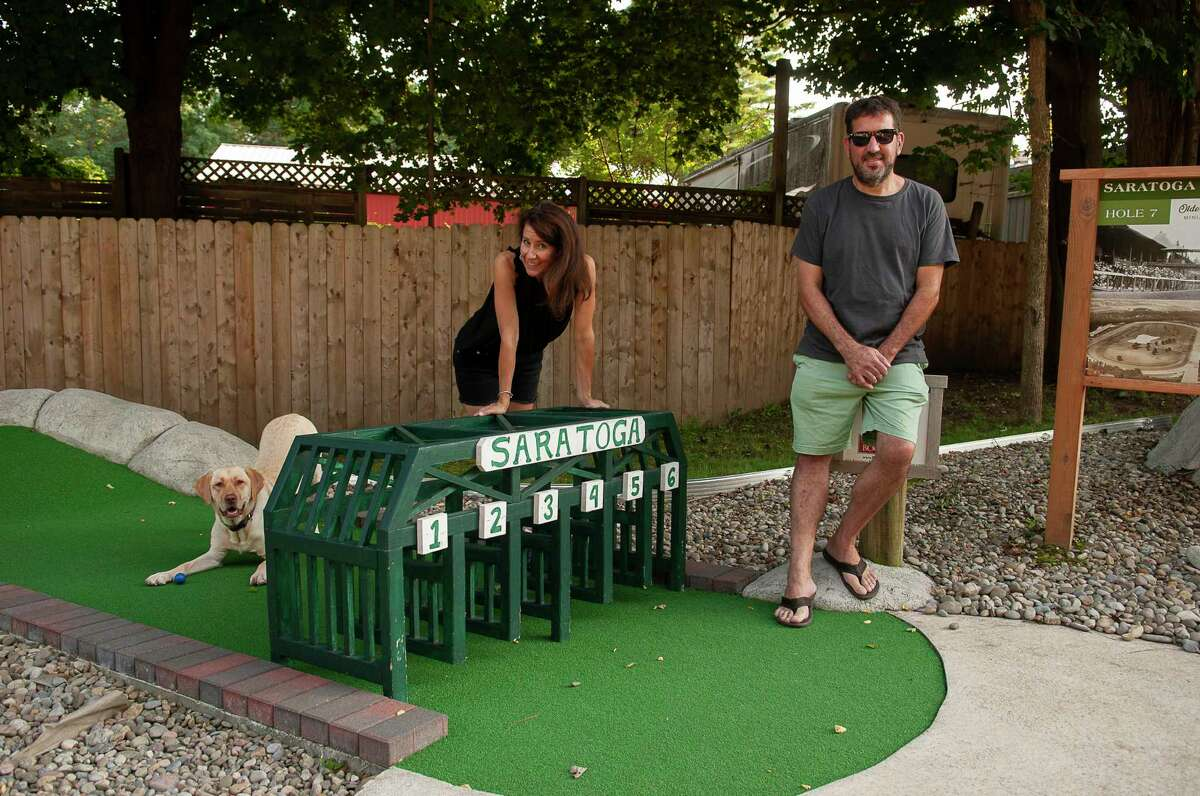 Olde Saratoga Mini Golf owner Brian Brumley and his girlfriend Kristen Eglintine pose with their dog, Lyla, on the course Tuesday prior to Puff Puff Putt night, Aug. 24, 2021 in Wilton, N.Y. (Jenn March, Special to the Times Union)