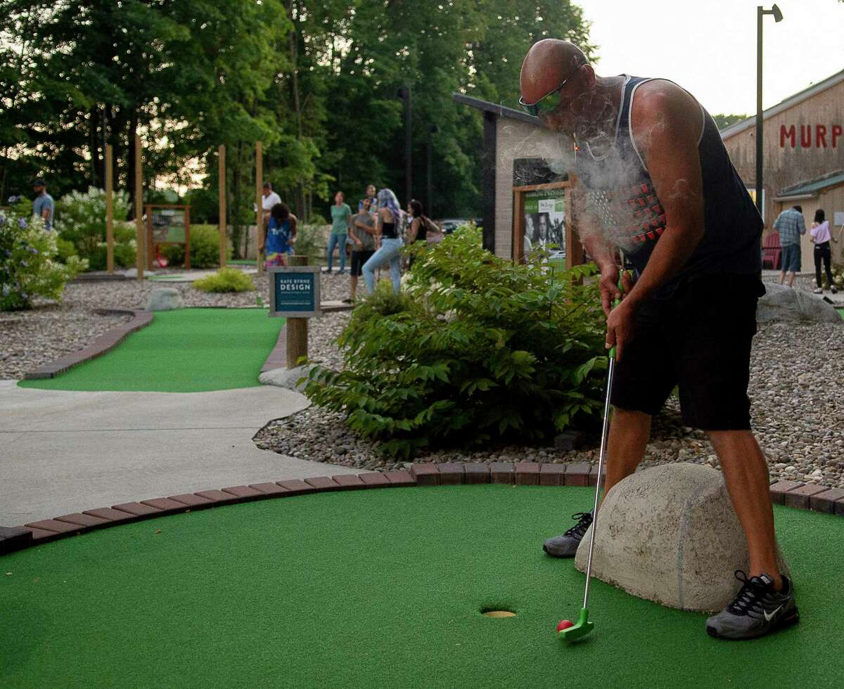 Paulie putts the ball as he smokes at Olde Saratoga Mini Golf's Puff Puff Putt night on Tuesday, Aug. 24, 2021 in Wilton, N.Y. (Jenn March, Special to the Times Union)