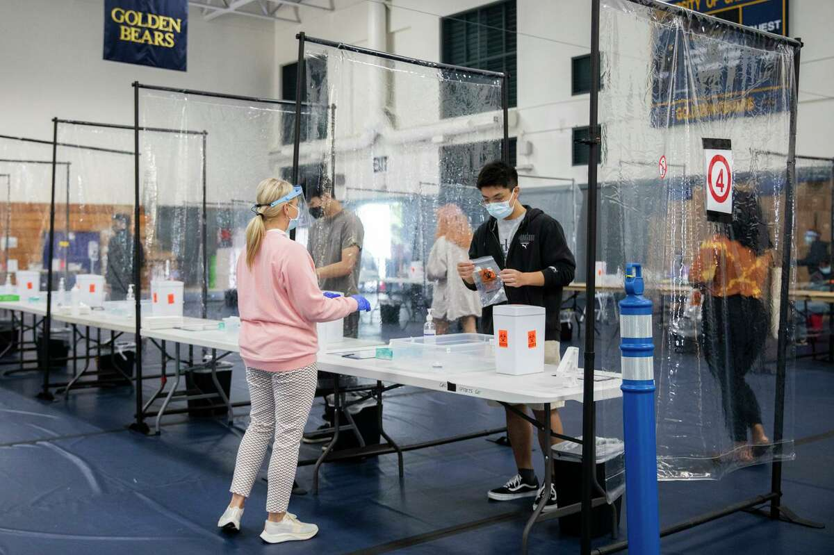 UC Berkeley students listen to instructions before conducting a self-COVID-19 test at a mass testing site set up in UC Berkeley's Tang Center.