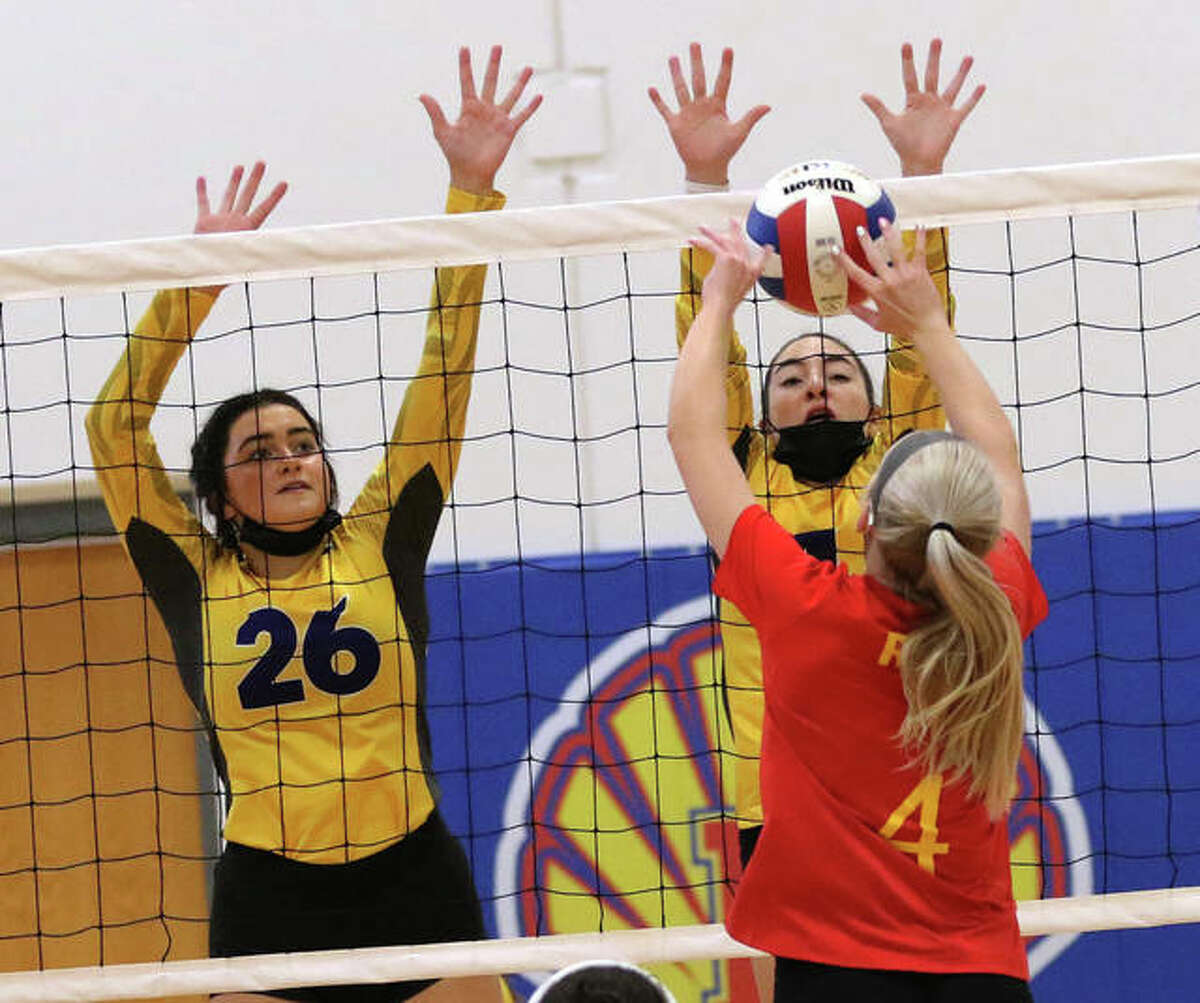Roxana's Aubrey Wiegand (4) pushes the ball over the block put up by Civic Memorial's Lexi Biciocchi and Camryn Gehrs (26) during pool play Tuesday night at Roxana Junior High in the 12th annual Roxana Invitational girls volleyball tournament.