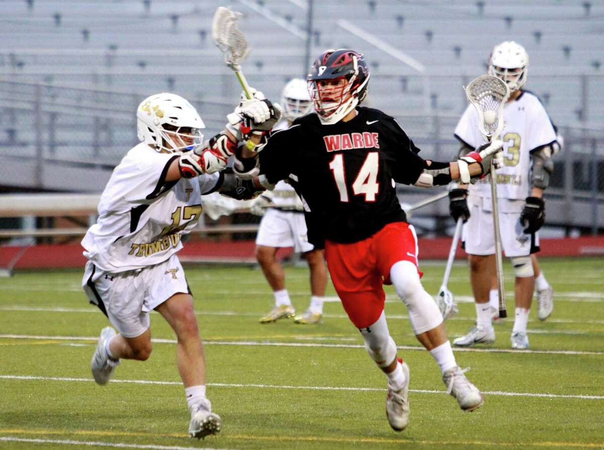 Fairfield Warde's Sam Palmer (14), right, drives towards the gaol as Trumbull's Jett Hughes (17) defends during boys lacrosse action in Trumbull, Conn., on Tuesday Apr. 24, 2018.