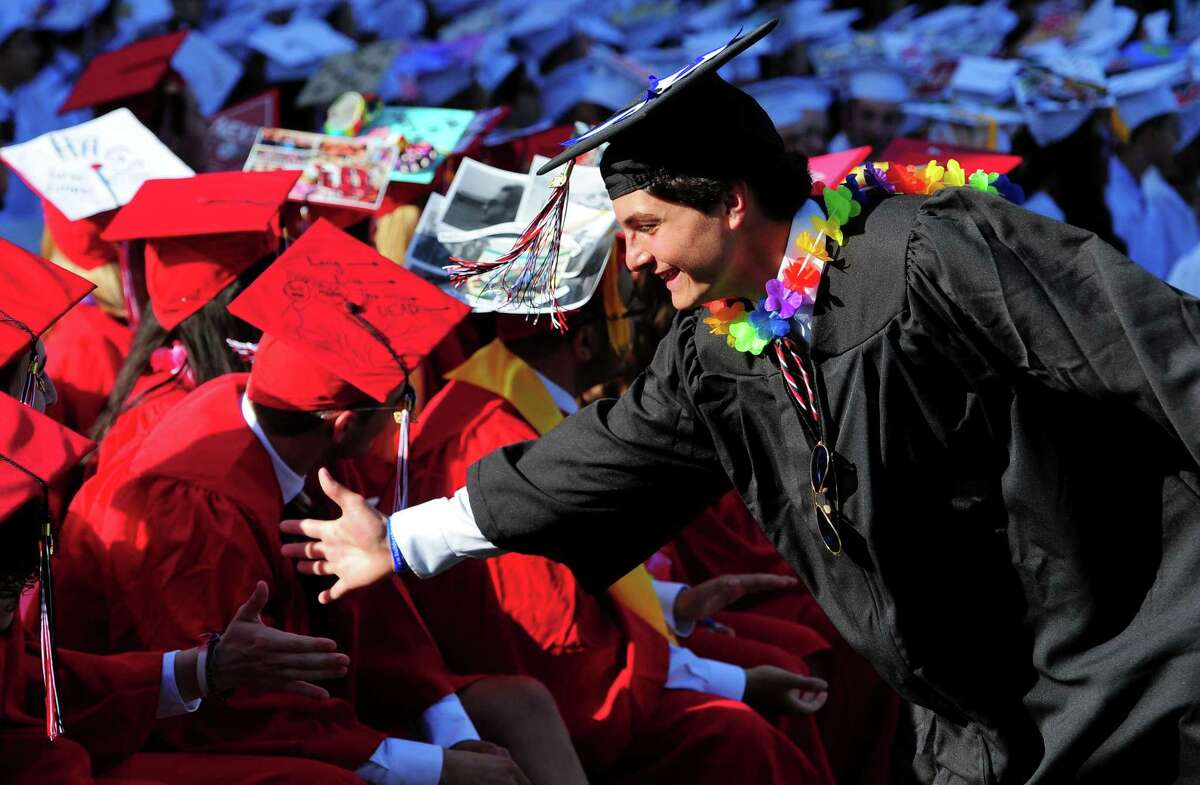 Graduate Sam Palmer goes along the front row greeting friends after getting his diploma during Fairfield Warde High School's Commencement Exercises in Fairfield, Conn., on Friday June 14, 2019.