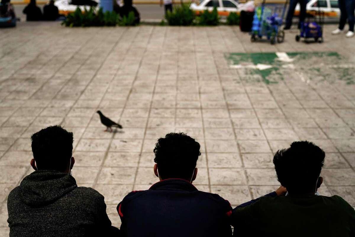 En esta foto de archivo del 13 de mayo de 2021, migrantes hondureños se sientan en una plaza en la frontera después de ser devueltos de Estados Unidos a México, en Reynosa, México.