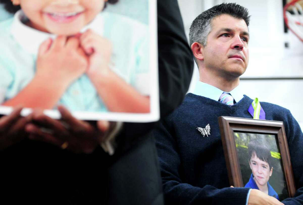 Ian Hockley (right) holds a photograph of his son, Dylan, at a press conference announcing the launch of Sandy Hook Promise at Edmond Town Hall in Newtown on 1/14/2013. Dylan was killed in the Sandy Hook Elementary School shootings. At left is a photograph of another victim, Ana Marquez-Greene. Photo by Arnold Gold/New Haven Register