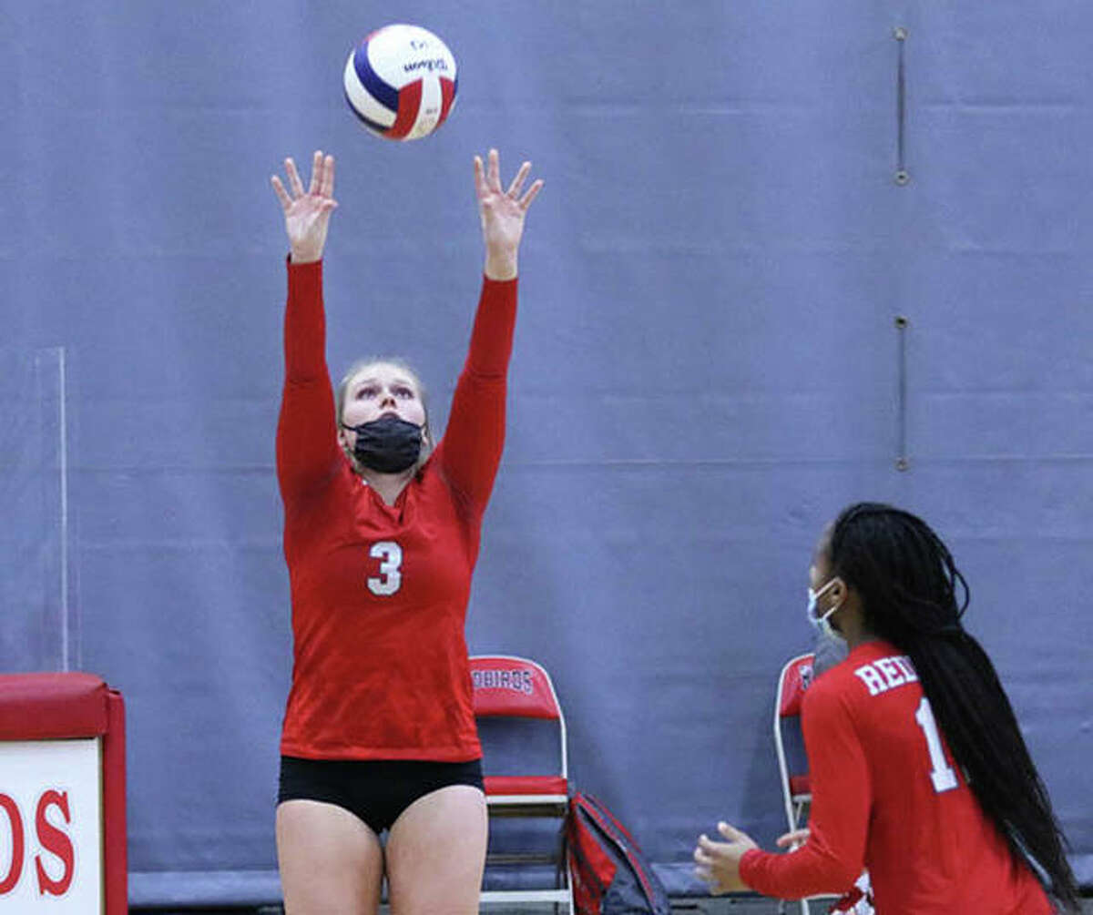 Alton's Taylor Freer (left) sets while teammate Renee Raglin heads to the net in a match last spring at Alton High. The Redbirds opened the 2021 season Tuesday night at home in Godfrey with a victory over Columbia.