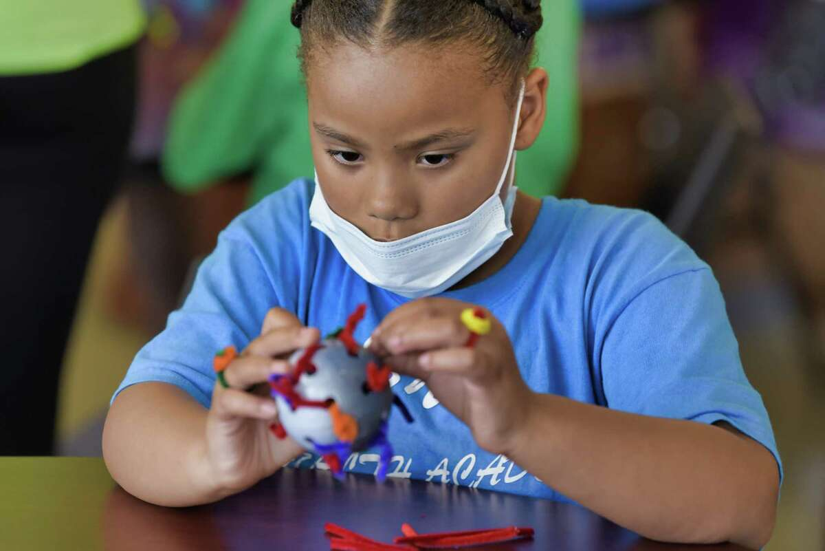 Aaliyah Schou, 7, of Albany uses pipe cleaners and a whiffle ball to create delta variant coronavirus model at the Black Nurses Coalition kid's health camp on Tuesday, Aug. 24, 2021, in Albany, N.Y.
