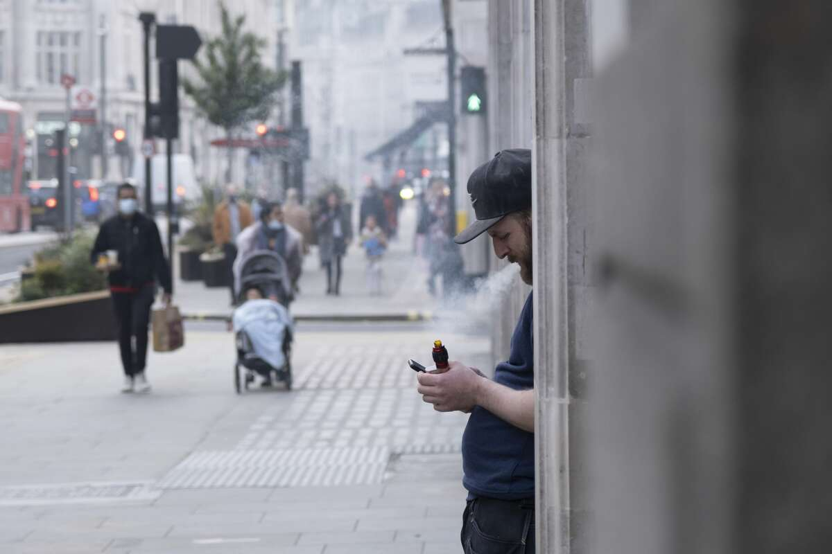 Man taking a break vaping while staring at his smart phone on Regent Street on 3rd March 2021 in London, England, United Kingdom. (Photo by Mike Kemp/In Pictures via Getty Images)