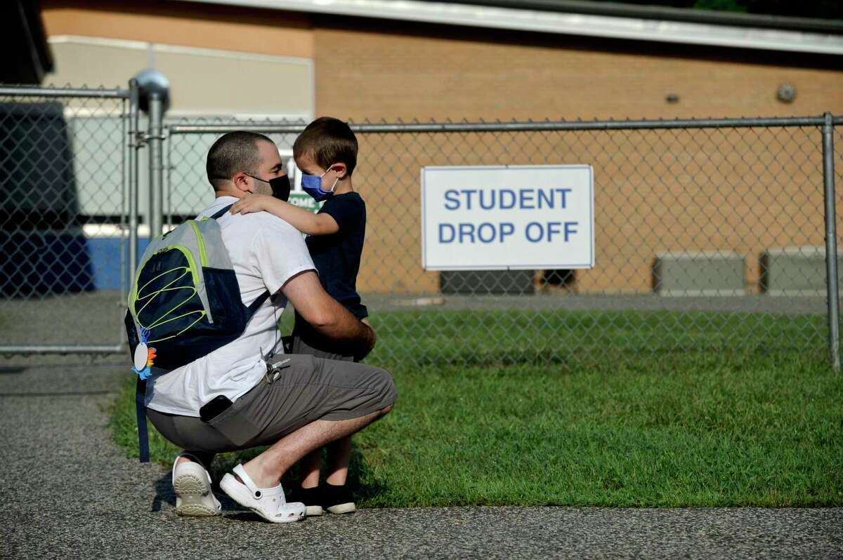 Willam Lopes, 5, waits with his father Elliott Lopes for the start of his first day of kindergarten. It was the first day of the new school year at Hill and Plain Elementary School, New Milford, Conn. Wednesday, August 25, 2021.