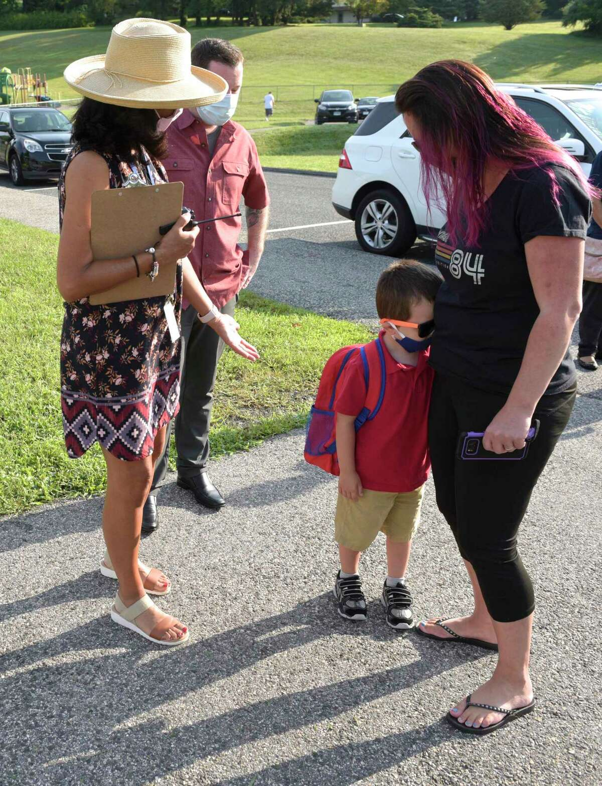 Heliett Sanches, school councilor, left, encourages Jackson Pettit, 5, to join her on the first day of the new school year at Hill and Plain Elementary School. Jackson's parents Laura and Chris Pettit offer support.New Milford, Conn. Wednesday, August 25, 2021. Jackson wore his special sunglasses for his first day of kindergarten.