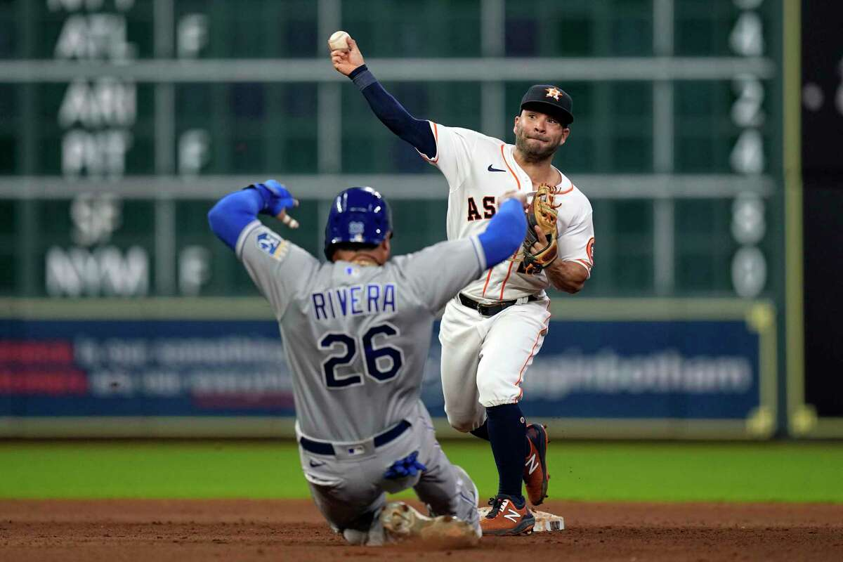 Houston Astros second baseman Jose Altuve, right, throws to first for a double play as Kansas City Royals' Emmanuel Rivera (26) slides into second base during the eighth inning of a baseball game Tuesday, Aug. 24, 2021, in Houston.