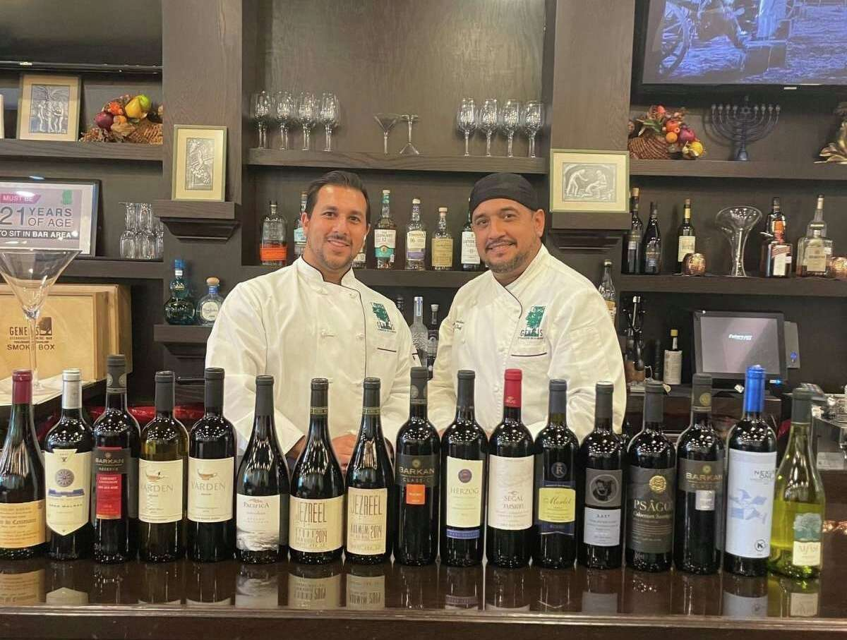 Founder Jason Goldstein, left, and executive chef Arturo Macias serve a large selection of kosher wine at Genesis in Meyerland.
