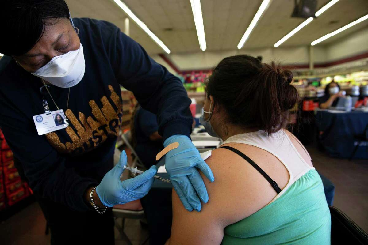 A Houston Health Department official administers a COVID-19 vaccine on Tuesday. Starting Thursday, people will get a combined $150 if they get both their shots from the Houston Health Department.