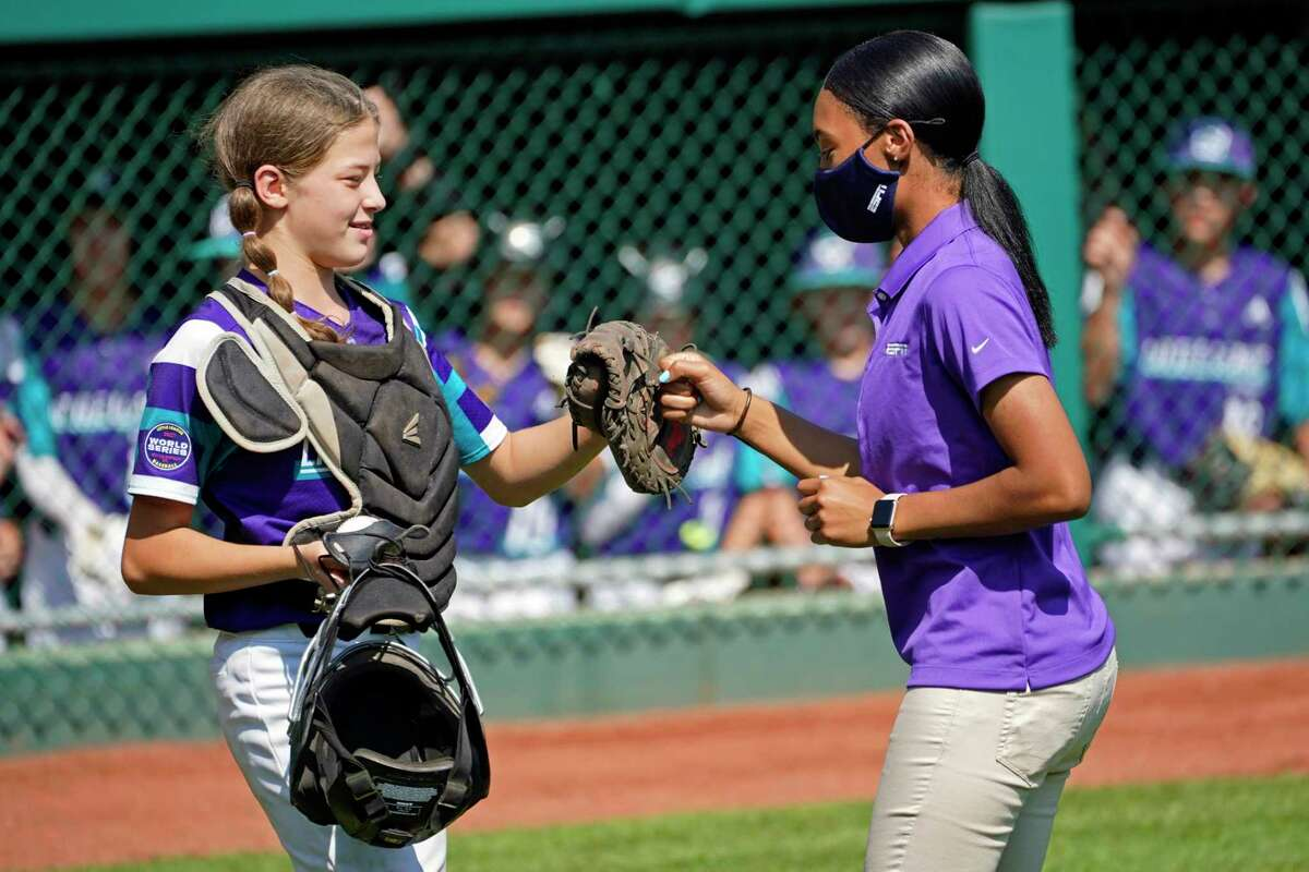 Abilene, Texas catcher Ella Bruning (8) fist bumps with Mo'ne Davis after Davis threw out the first pitch for the game between Abilene, Texas and Toms River, N.J. during a baseball game at the Little League World Series tournament in South Williamsport, Pa., Tuesday, Aug. 24, 2021. (AP Photo/Tom E. Puskar)