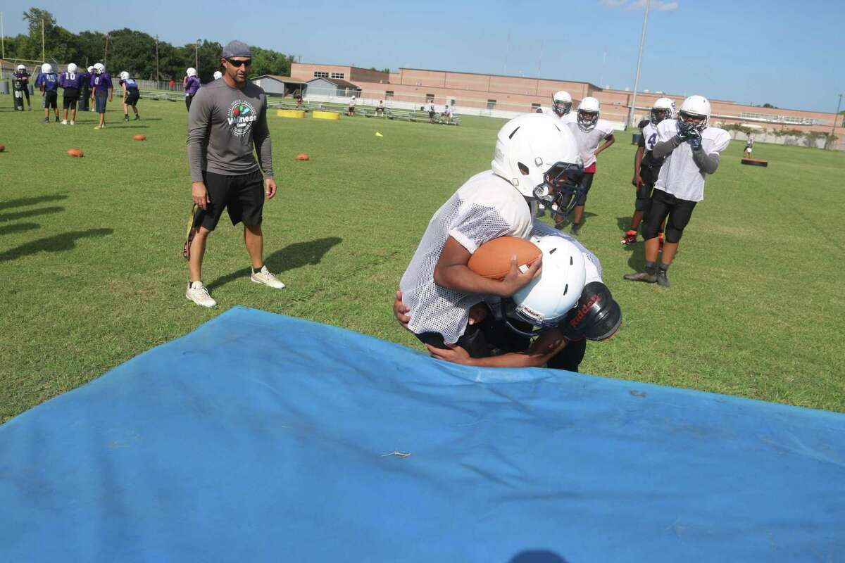 Longtime Southmore Intermediate football coach Eric Lewis watches two of his eighth graders fall onto a mat for a drill.