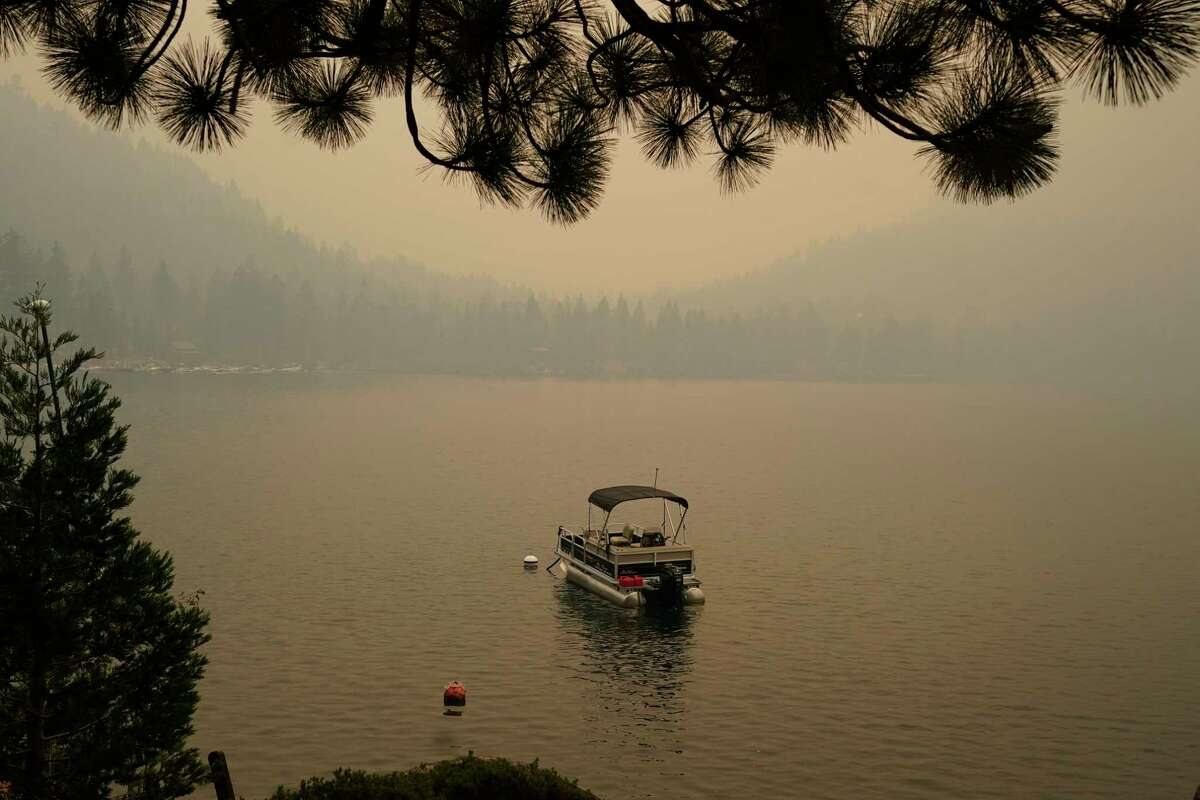 Smoke from the Caldor Fire shrouds Fallen Leaf Lake near South Lake Tahoe, Calif., Tuesday, Aug. 24, 2021. The massive wildfire that is over a week old has scorched more than 190 square miles, and destroyed hundreds of homes since Aug. 14. It is now less than 20 miles from Lake Tahoe.