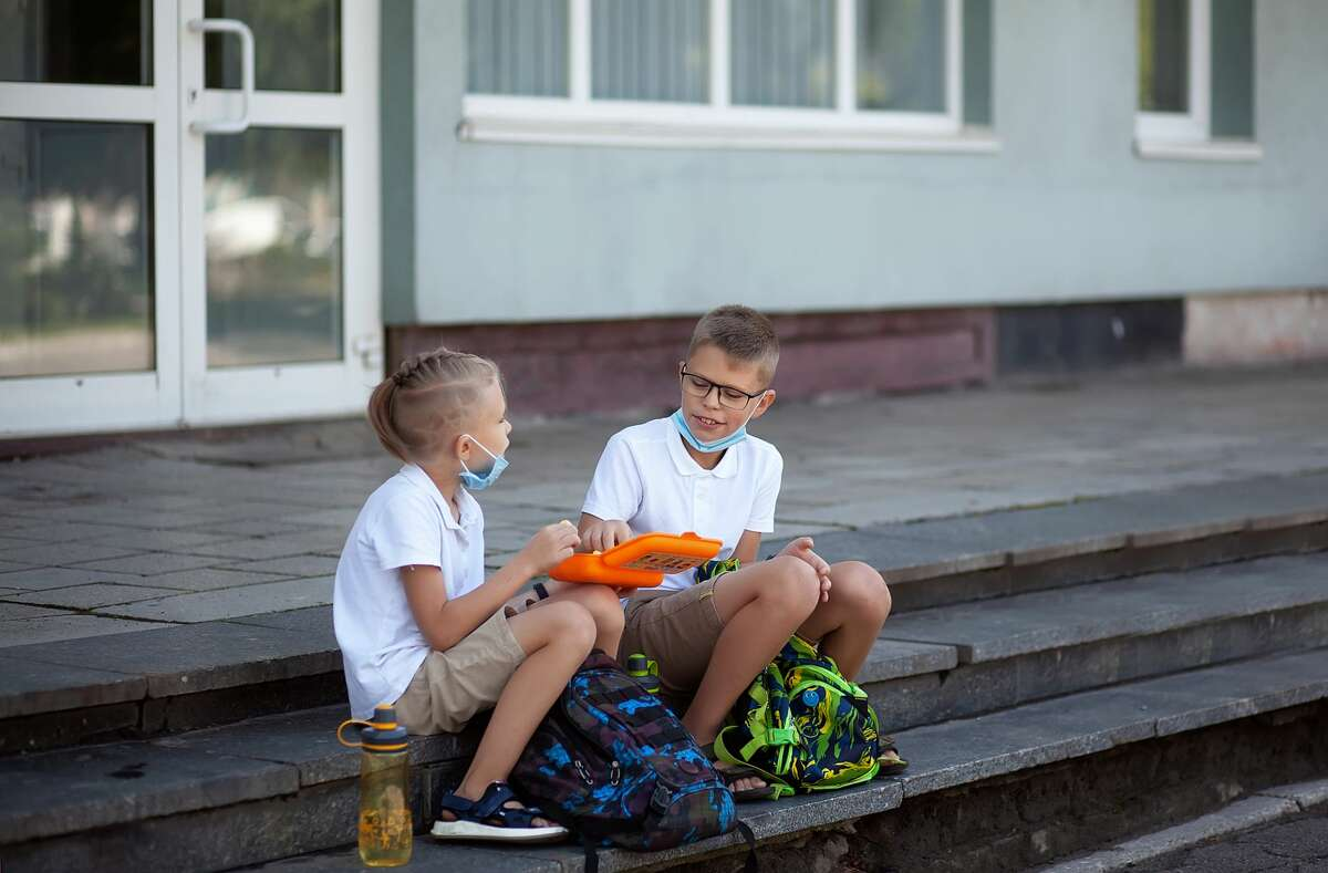 Boys wear masks to protect against coronavirus sit on the steps of the school and eat lunch.
