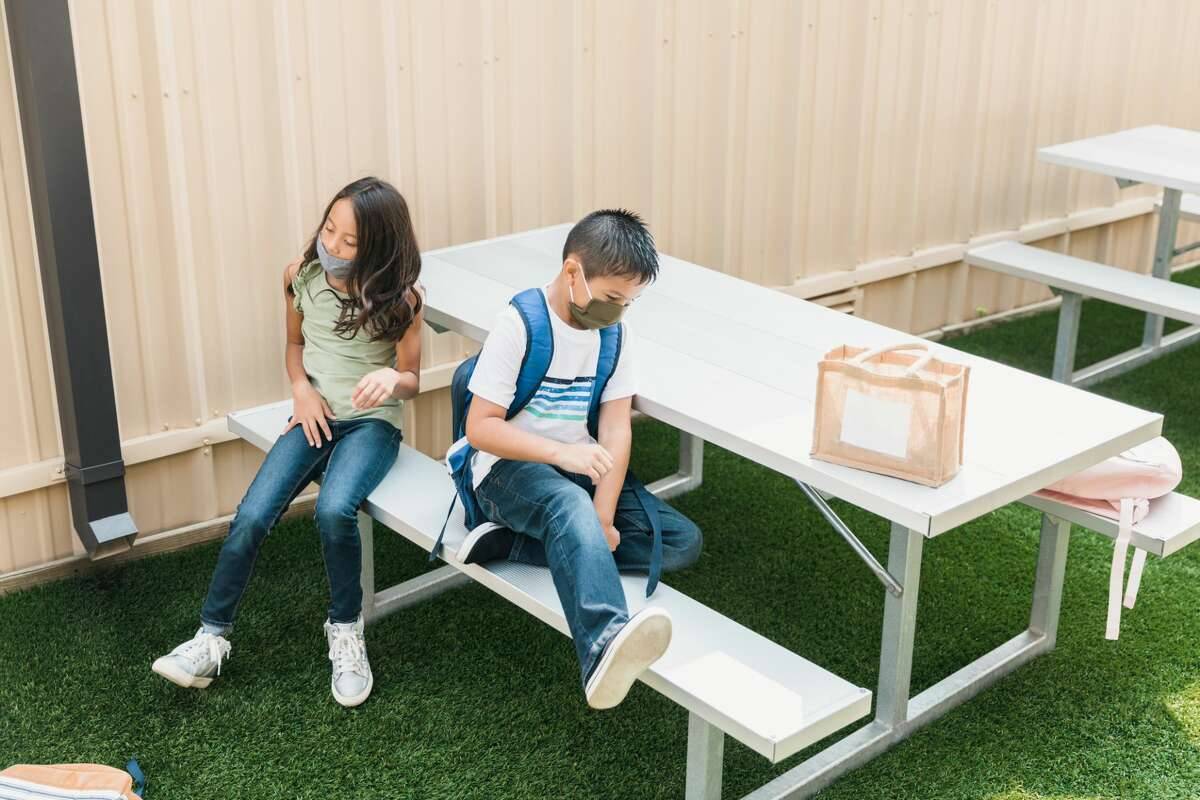 Two elementary school students sit down at a picnic table outdoors in the schoolyard.