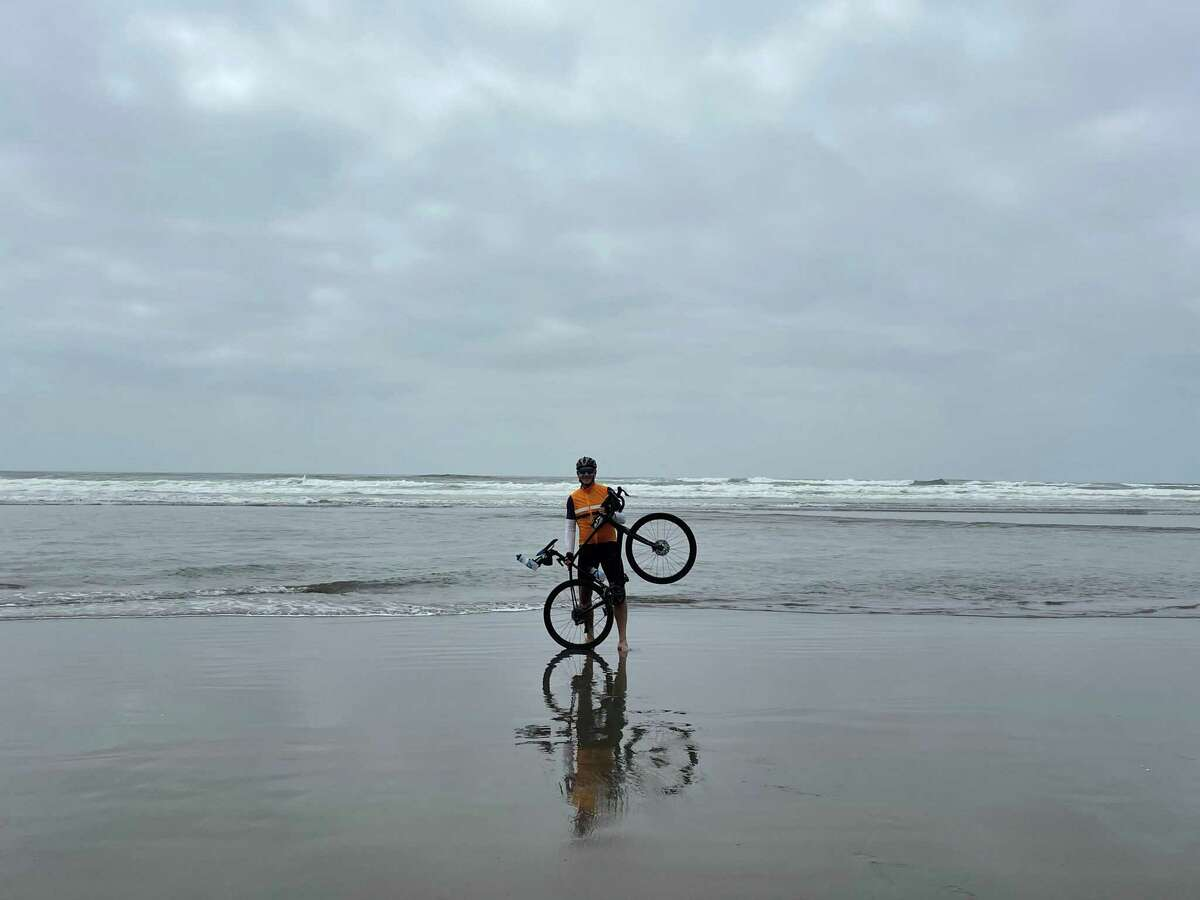 Alan Masarek dips his rear wheel in the Pacific Ocean to begin his 3,800-mile cross-country bike ride to raise awareness and funds for Empower House.