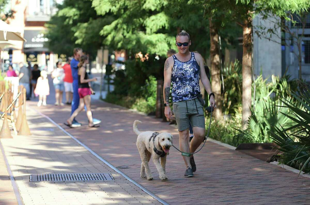 Oliver McGuire and his Goldendoodle, Noodle, take a walk at Pearl. McGuire and Noodle live at the nearby Southline Residences.