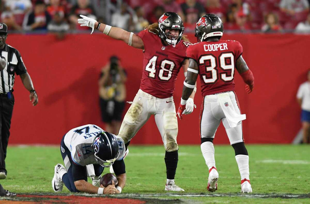 Tampa Bay Buccaneers linebacker Grant Stuard (48) celebrates with defensive back Chris Cooper (39) after sacking Tennessee Titans quarterback Matt Barkley (14) during the second half of an NFL preseason football game Saturday, Aug. 21, 2021, in Tampa, Fla. (AP Photo/Jason Behnken)