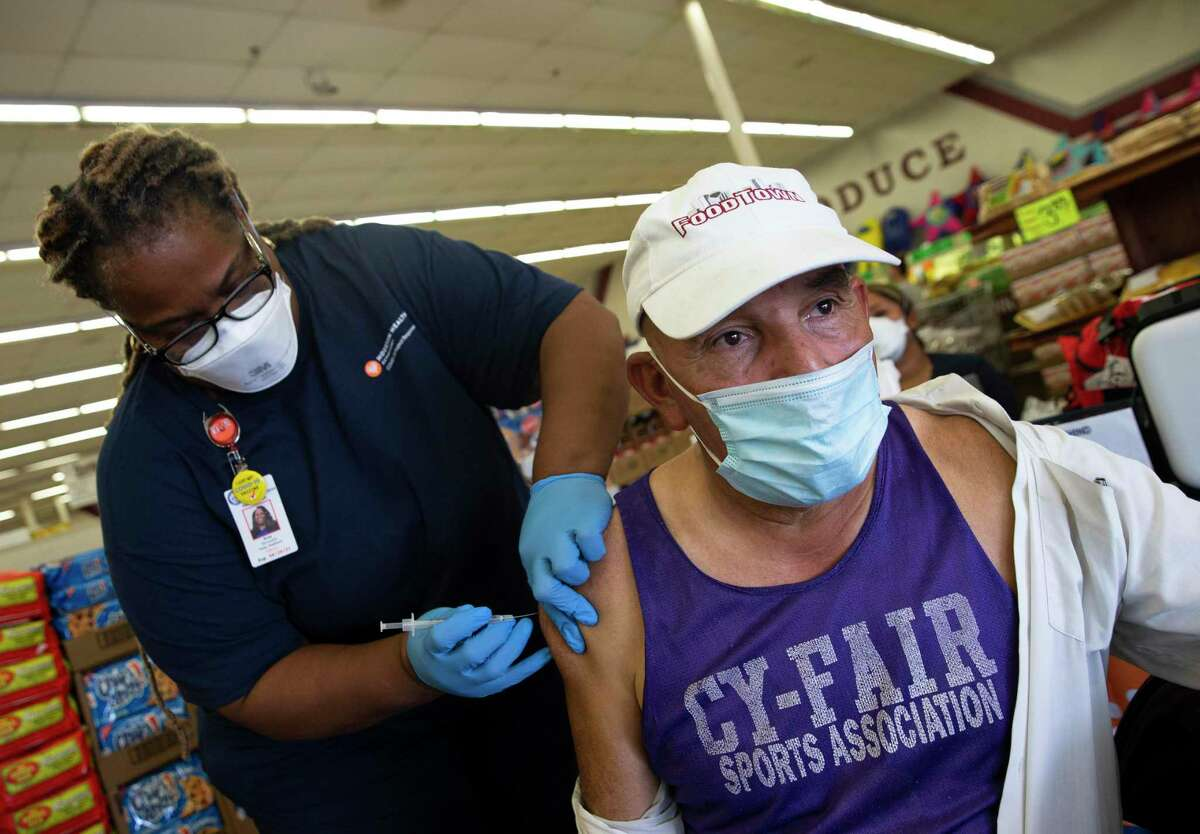 Terraceda Gray, a LVN at Houston Health Department, administers a COVID-19 vaccine to Jose Luis Morales, 67, at a Food Town market Tuesday, Aug. 24, 2021, in Houston. Morales, an employee at Food Town, was getting his second dose of the vaccine.