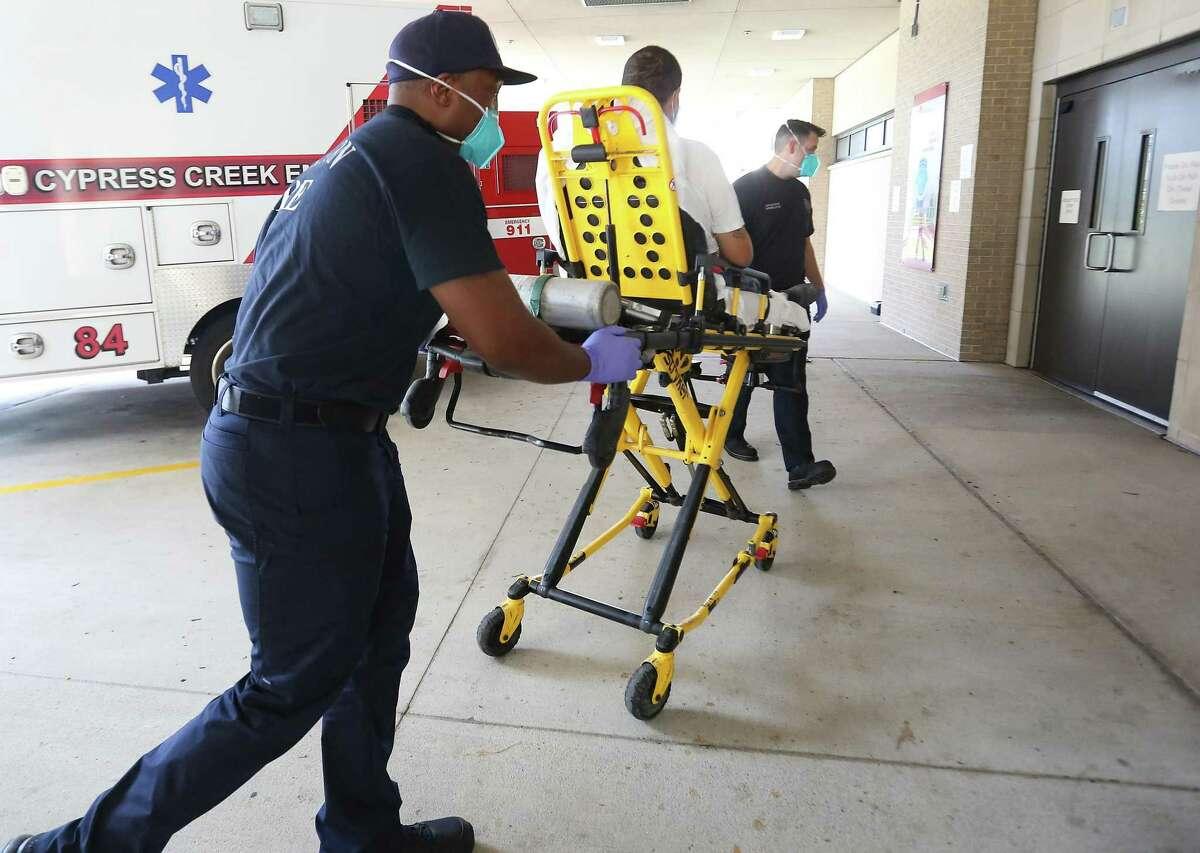 "Houston Fire Dept. paramedics Valentin ""Beau"" Beauliere, left, and Josh Walls, take a patient to Houston Northwest Medical Center on Thursday, Aug. 19, 2021."