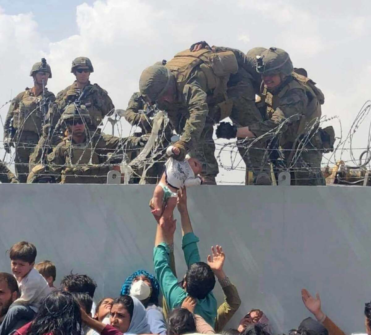 In this image from video provided by Omar Haidari. a baby is being lifted across a wall at Kabul Airport in Afghanistan by US soldiers.