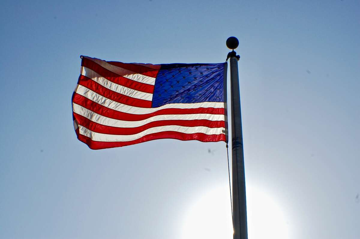 FILE - The American flag flaps in the wind as the sun rises in above the eastern banks of the Mississippi River.