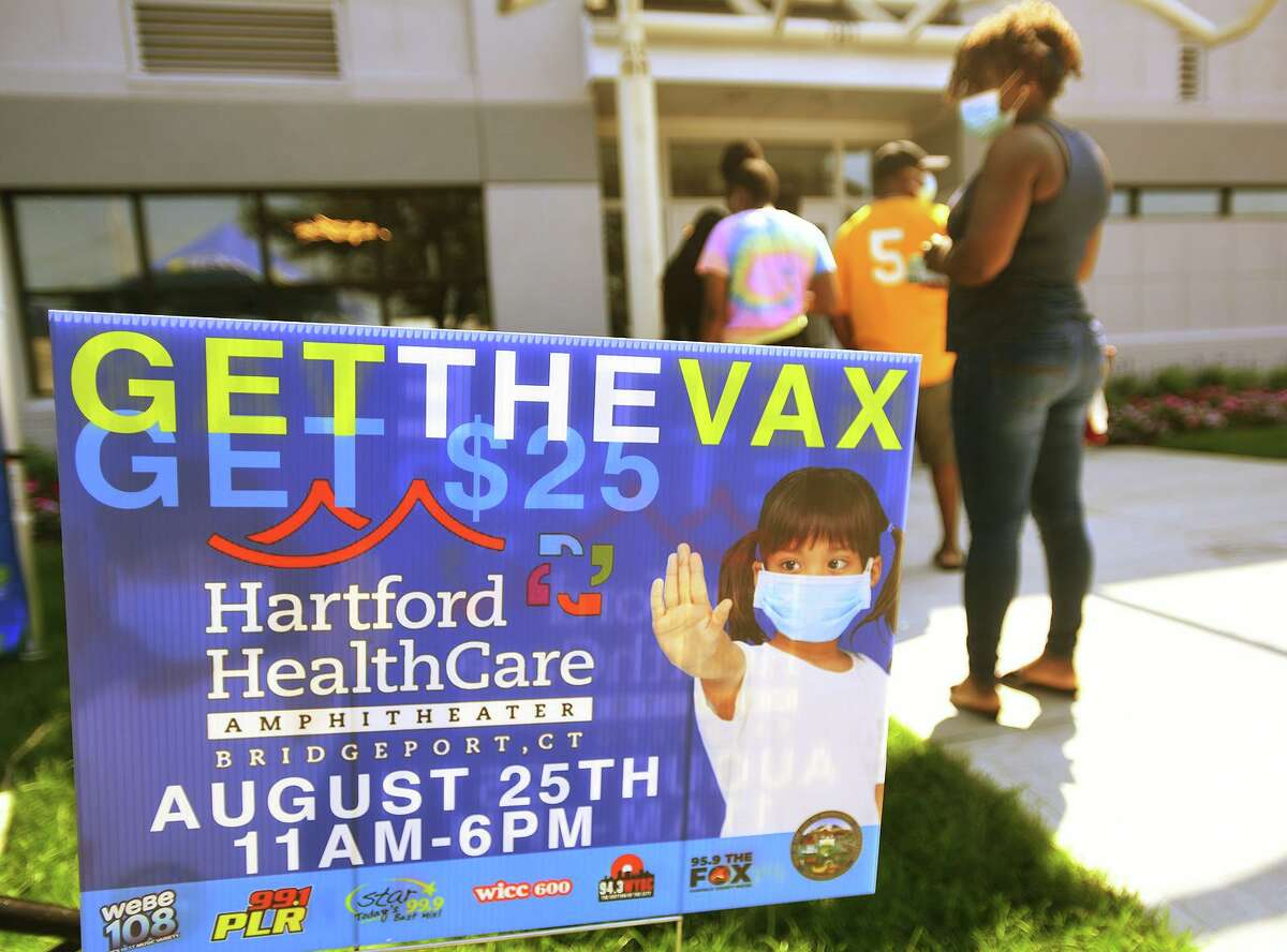 The line reaches out the door for a free COVID-19 vaccination clinic at the Hartford Healthcare Amphitheater in Bridgeport, Conn. on Wednesday, August 25, 2021.