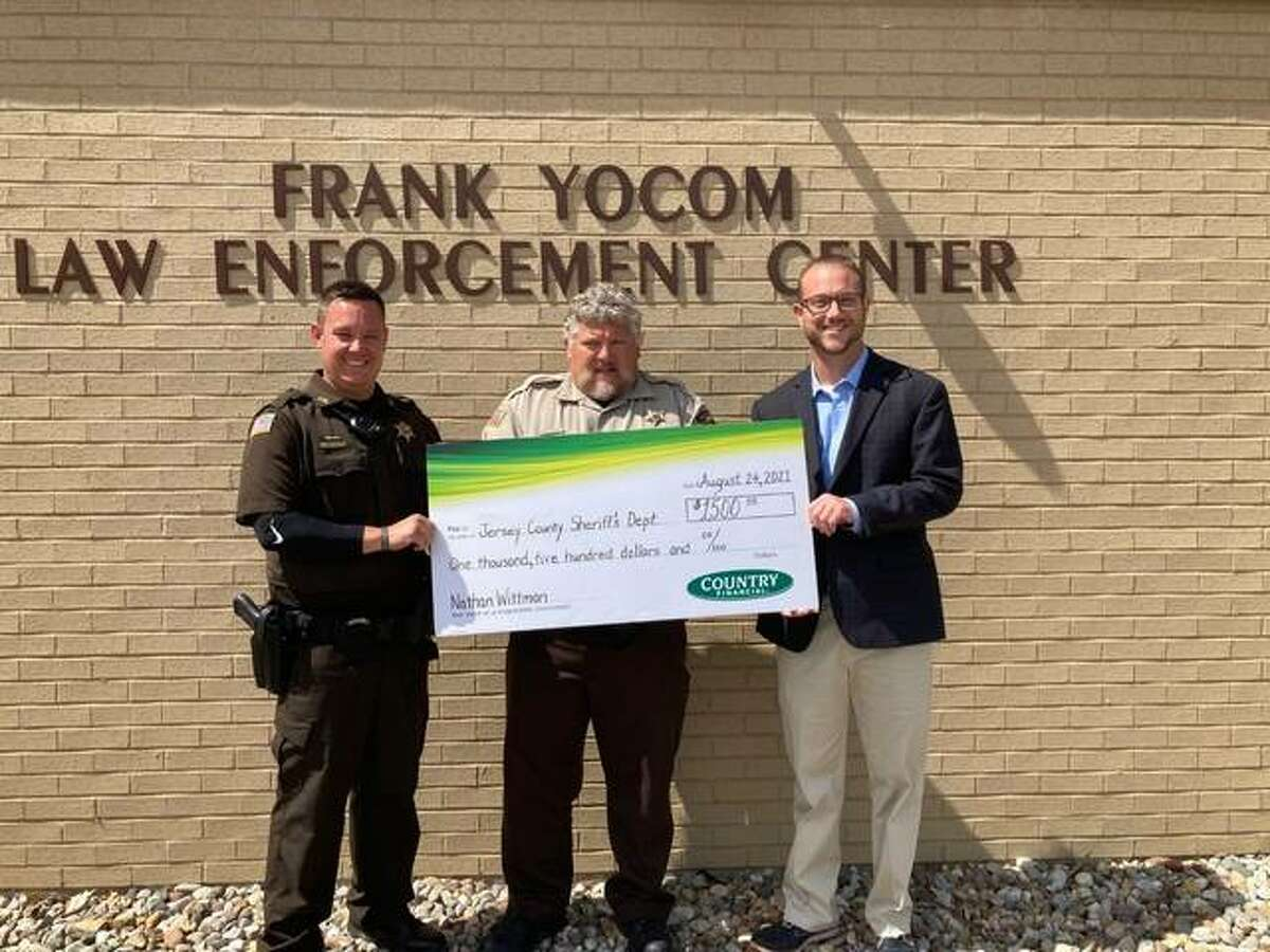 COUNTRY Financial Representative Nathan Wittman, right, of Shelbyville, presents a $1,500 Operation Helping Heroes donation to Jersey County Sheriff Mike Ringhausen, center, and Deputy Jamison Metcalfe, left, to help purchase new cameras.